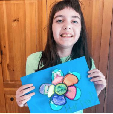 Comprehensive Autism School student holding up artwork